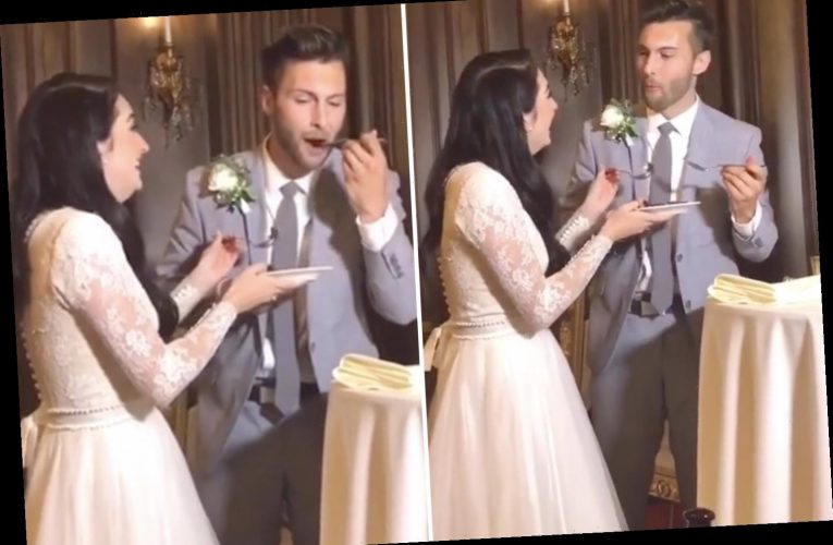 Hilarious moment groom ruins wedding cake tradition by tucking into his own slice – leaving his bride stunned – The Sun