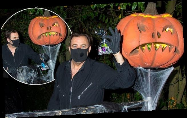 Jonathan Ross greets trick-or-treaters at his home